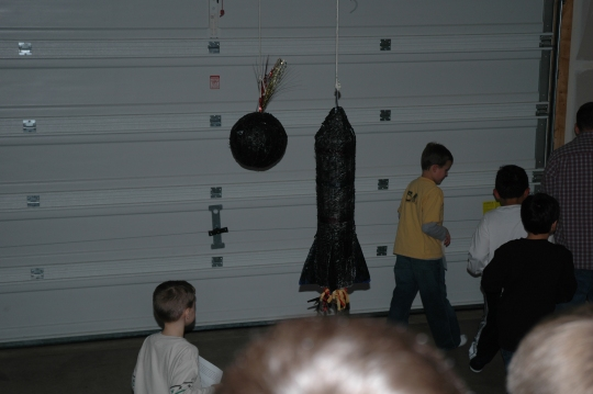 A soccer ball and a space shuttle pinata spray painted black to look like bombs and missiles.
