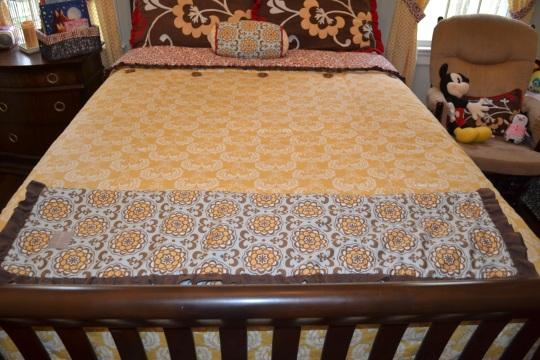 Her crib quilt is folded at the foot of the bed